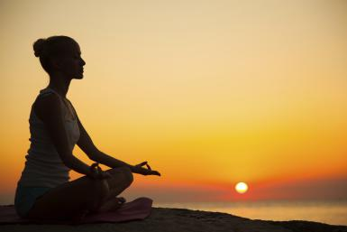 woman doing meditation at sunset